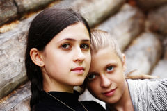 A pair of sisters. Looking into the camera on a woody background Stock Photo