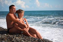Pair sit on pebble beach Stock Images