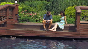 Pair sit on a wooden bridge and looking at the lake where ducks swim. stock footage