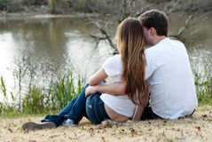 Pair sitting on bank of lake Royalty Free Stock Photos
