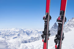 Pair of skis on snow. Pair of red skis standing in snow with copy space. Closeup of the ski touring equipments on the top of the mountain with copy space. Winter stock images