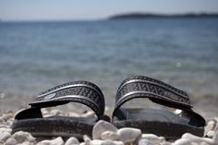 Pair of slippers on a beach. Istria, Croatia - April 20th, 2019 - Pair of slippers on a beach with sea in background royalty free stock photography