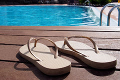 Pair of slippers by a swimming pool Royalty Free Stock Image