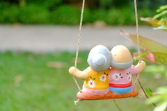 A pair of small beautiful old man and woman statues sitting on a swing stock photography