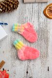 Pair of handmade woolen socks for newborn. Pair of small and cute handmade woolen socks for newborn, on white wooden background royalty free stock photos