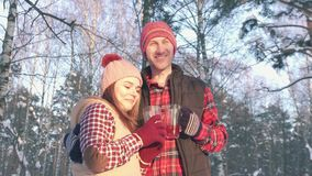 Couple of smiling young people in winter in the park at sunset drinking hot mulled wine. A pair of smiling young people in winter clothes in a snow-covered park stock video footage
