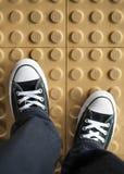A pair of sneaker on non slip flooring. Walking with a pair of black sneaker on a yellow non slip floor stock image