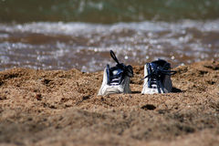 Pair of sneakers on beach Stock Images