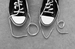 Pair of sneakers with laces bound together as I love you stock photos