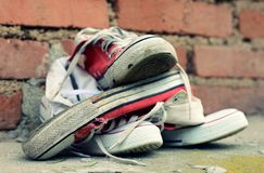 Pair sneakers leaning against a brick wall Stock Images
