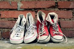 Pair sneakers leaning against a brick wall Stock Photos