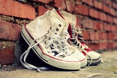 Pair sneakers leaning against a brick wall Royalty Free Stock Image