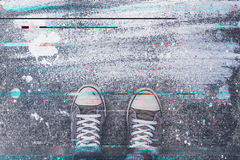 Pair of sneakers on pavement with digital glitch effect Stock Photos