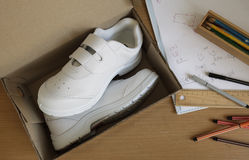 Pair of sneakers in shoe cardboard box on student table. Stock Photos