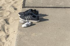 Two pair of sport shoes. Standing on a concrete slab near the beach royalty free stock photo