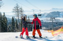Pair of snowboarders on top ski resort at sunny day stock photos