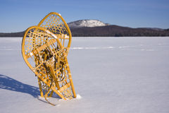 Pair of Snowshoes in the Snow. Two snowshoes standing in the snow with mountains in background Royalty Free Stock Images