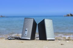 A pair of speakers on the beach with blue sea water in the background ready for beach party on a sunny day. stock photo