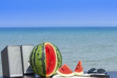Pair of speakers, whole and cut watermelon with knife and wooden cutting board and a pair of sunglasses on the beach in summer rea royalty free stock images