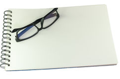 Pair of spectacles lying closed on a sketch book. Pair of dark framed spectacles lying closed on a spiral wire bound blank white sketch book in one corner with Royalty Free Stock Photos