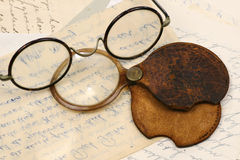 A pair of spectacles and a magnifying glass. On old letters Stock Image