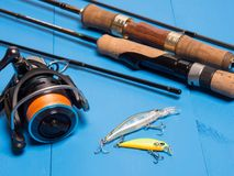 A pair of spinnings, a reel and baits on a blue wooden background.Top of view royalty free stock photography