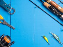 A pair of spinnings, a reel and lures on a blue wooden background.Top of view. Copy space. royalty free stock photos