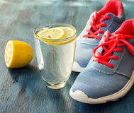 Pair of sport footwear, sneakers, glass of detox water, health c Royalty Free Stock Images