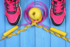 Pair of sport shoes, fresh apple and accessories for fitness on blue boards, copy space for text Stock Photo