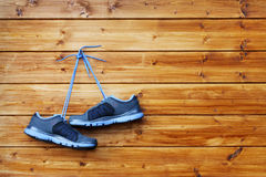 Pair of sport shoes hang on a nail on a brown wooden wall Stock Photos