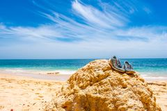 Pair of sport shoes lying on stone on beach against blue sky. Praia de Marinha in Algarve, Portugal stock images