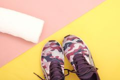 Pair of sport shoes and towel on colorful background. Royalty Free Stock Image