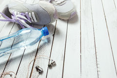 Pair of sport shoes, water bottle and earphones on white wood Royalty Free Stock Photos