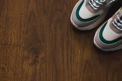 Pair of sport shoes on wooden background. New sneakers and space for ad text stock image