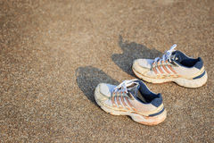 Pair of sports shoes standing on a tartan race track Royalty Free Stock Photos