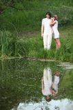 Pair stands on bank of pond Royalty Free Stock Photo