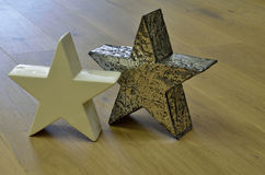 Pair of stars on wooden floor. One star made out of china, the other one made out of metal Royalty Free Stock Images