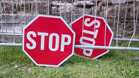 A pair of stop signs. Placed on the grass stock photos