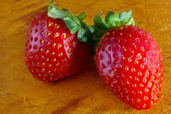 A pair of straberries. On wooden chopping board Royalty Free Stock Photos