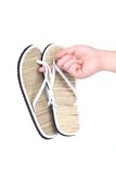 Pair of striped flip-flop sandals in hand. Stock Image