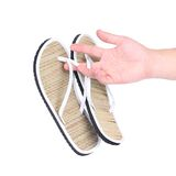 Pair of striped flip-flop sandals in hand. Royalty Free Stock Photos