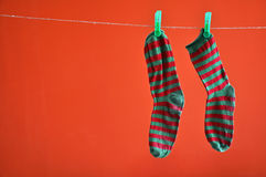 Pair of striped socks hanging on a rope isolated on red. Background stock images