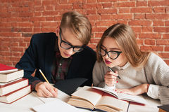 Pair of students carefully reading textbook. Young men explain girl hard material in book. Education, brainstorm, teamwork, graduation project concept Stock Photos