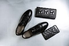 Black perforated shoes oxfords, a purse and a phone case on a paper white background stock photography