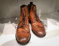 Pair of stylish brown leather boots closeup shot. Laces, white background. Vintage royalty free stock images