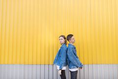 Pair of stylish people standing backs against the background of the yellow wall. Hipsters photo. Minimalist portrait of a beautiful pair on a yellow background stock photo