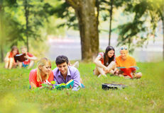 Pair successful students with a textbook in a Park Royalty Free Stock Photos