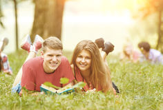 Pair successful students with a textbook in a Park Stock Photos