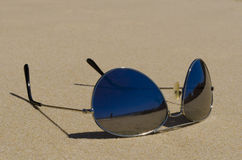 Pair of sunglasses on beach sand closeup. Details of a pair of dark tinted sunglasses on beach sand. Lenses have dark mirror-like reflective surface and stock images