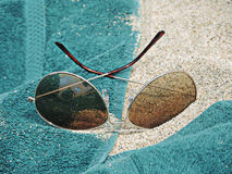 Pair of Sunglasses Sitting on Beach Towel in Sand. Metal framed sunglasses rest in sand and a green beach towel Stock Images